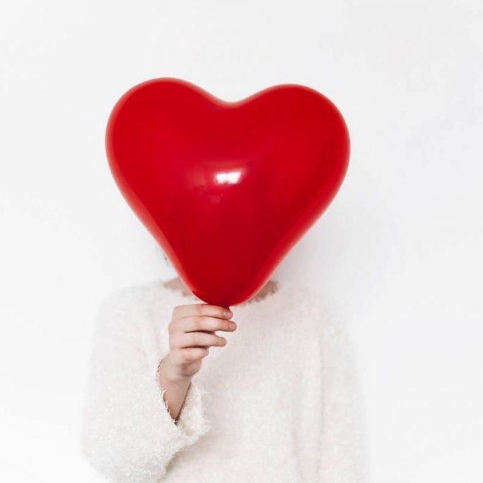 hand holding heart balloon